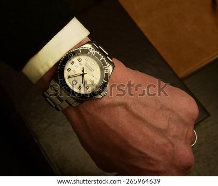 NEW YORK CITY - APRIL 1 2015: Victorinox Swiss Army Watch with trademark black enamel unidirectional bezel atop suede-bound book - stock photo