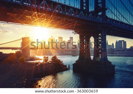 New York City - beautiful sunset over Manhattan bridge with Manhattan and Brooklyn bridge   - stock photo
