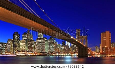 New York City Brooklyn bridge and Manhattan skyline night scene over Hudson River - stock photo