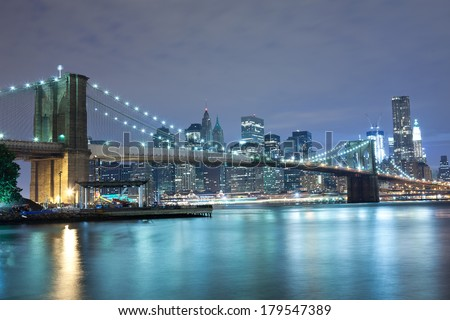 New York City Brooklyn Bridge skyline with skyscrapers over Hudson River illuminated with lights at dusk. - stock photo