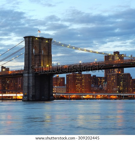 New York City Brooklyn Bridge with downtown skyline over East River at dusk - stock photo