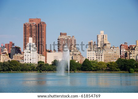 New York City Central Park fountain and urban Manhattan skyline with skyscrapers and trees lake reflection with blue sky and white cloud. - stock photo