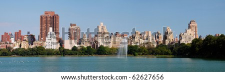 New York City Central Park panorama in Manhattan over lake with skyscrapers and fountain with trees and reflection. - stock photo