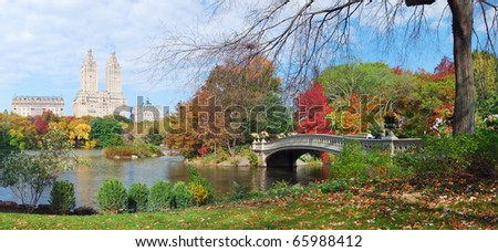 New York City Central Park panorama view in Autumn with Manhattan skyscrapers and colorful trees with Rainbow Bridge over lake with reflection. - stock photo