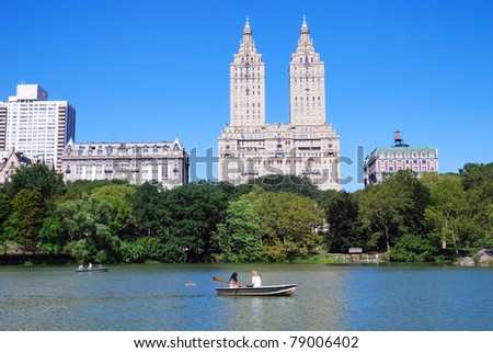 New York City Central Park with Manhattan skyline skyscrapers and blue sky with boat in lake. - stock photo