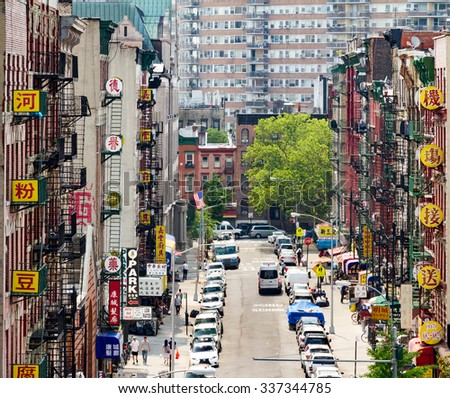 NEW YORK CITY - CIRCA JULY 2015: Cars and signs line a busy street in Chinatown during the Fourth of July holiday in Manhattan, New York City. - stock photo