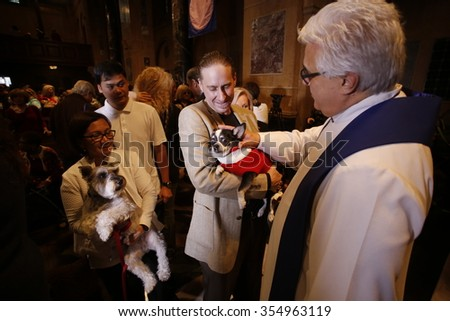 NEW YORK CITY - DECEMBER 13 2015: Cindy Adams & commissioner William Bratton hosted the seventh annual Blessing of the Animals at Christ Church in Manhattan. Minister Stephen Bauman confers blessing - stock photo