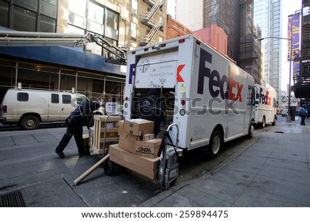 NEW YORK CITY - FEB. 25, 2015:  FedEx drivers unload two delivery vans in midtown Manhattan. FedEx Corporation is an American global courier delivery services company 