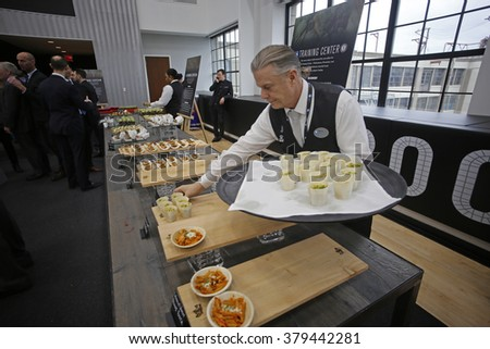 NEW YORK CITY - FEBRUARY 17 2016:  Bill de Blasio joined management of the Brooklyn Nets to open the NBA franchise's new training facility. Setting out hors d'oeuvres from on site kitchen - stock photo