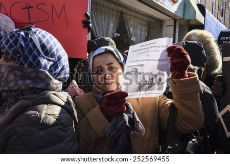 NEW YORK CITY - FEBRUARY 13 2015: Members of the Muslim community staged a vigil to call for justice in the killing of three Muslim Chapel Hill students.Female activist with pictures of slain students - stock photo