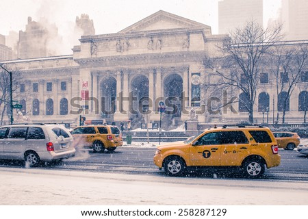 NEW YORK CITY - FEBRUARY 21, 2015:  Snow falling outside historic New York Public Library in Manhattan as cars go by.  - stock photo