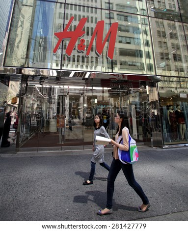 NEW YORK CITY - FRIDAY, MAY 8, 2015: Pedestrians walk past a H&M clothing retail store in Manhattan. H & M Hennes & Mauritz AB (H&M) is a Swedish multinational retail-clothing company.    - stock photo