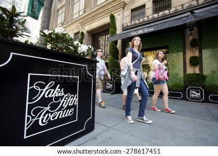 NEW YORK CITY - FRIDAY, MAY 8, 2015: Pedestrians walk past Saks Fifth Avenue in Manhattan. Saks Fifth Avenue is an American department store chain owned by the Hudson's Bay Company. - stock photo