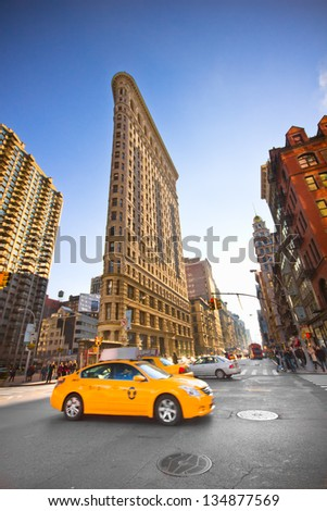 NEW YORK CITY - JAN 6: Yellow Taxi and Historic Flatiron Building in NYC as seen on Jan 6, 2013 in New York City.This iconic triangular building located in Manhattan's Fifth Ave was completed in 1902. - stock photo