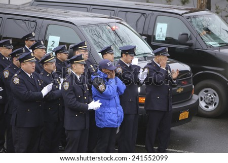 NEW YORK CITY - JANUARY 4 2015: several thousand police officers from all over North America attended funeral services for slain NYPD officer Wenjian Liu in Brooklyn.NYPD honor guard listens to eulogy