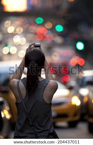 New York City - July 11, 2014: A girl was standing at the middle of 42nd Street in Manhattan and holding her cell phone and waiting to capture the Manhattanhenge.  - stock photo