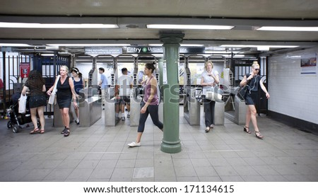 NEW YORK CITY - JULY 1, 2012: Commuters in subway station. The NYC Subway is one of the oldest and most extensive public transportation systems in the world, with 468 stations.  - stock photo