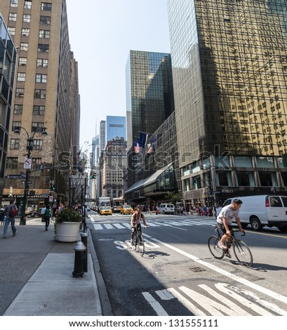NEW YORK CITY - JULY 12: Cyclists and cars drive down 42nd street on July 12, 2012 in Manhattan, New York. Manhattan is a major commercial, economic, and cultural center of the United States.