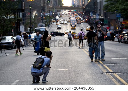 New York City - July 11, 2014: Group of people and photographers were standing at the middle of 42nd Street and blocking the road in Manhattan and waiting to capture the Manhattanhenge. - stock photo