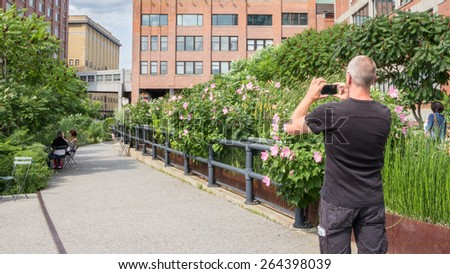 NEW YORK CITY - JULY 29,2014: Man making a picture in High Line Park in New York. The High Line is a public park built on an old railway track elevated above the streets of Manhattan. - stock photo