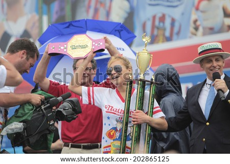 NEW YORK CITY - JULY 4 2014: Nathan's Famous held its annual Fourth of July Hotdog Eating Contest in Coney Island, Brooklyn despite moderate rain from Hurricane Arthur. Miki Sudor with belt & trophy