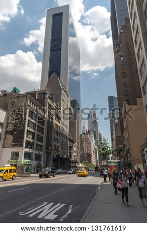 NEW YORK CITY - JULY 12: People walk down 57th street on July 12, 2012 in Manhattan, New York. Manhattan is a major commercial, economic, and cultural center of the United States. - stock photo