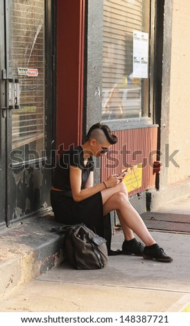 NEW YORK CITY  - JULY 27: Unidentified woman in Soho on July 27, 2013. SoHo is a neighborhood in Lower Manhattan, New York City, notable for being the location of many artists  lofts and art galleries - stock photo