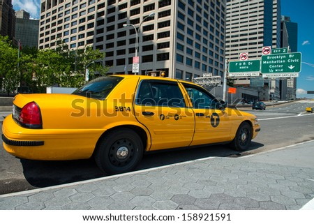 NEW YORK CITY -  JUN 14: Yellow taxi speeds up in Manhattan streets, June 14, 2013 in New York City.  Yellow cars serve as taxis in NYC and are easy to spot among other vehicles because of their color - stock photo