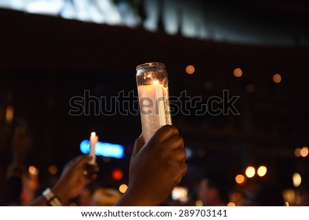 NEW YORK CITY - JUNE 21 2015: Brooklyn borough president Eric Adams hosted a candlelight vigil at the Barclay's Center on behalf of victims of the Emanuel A.M.E massacre. Candles held aloft. - stock photo