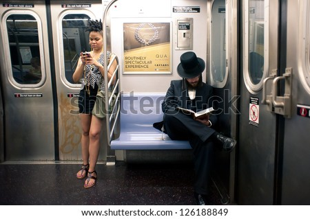 NEW YORK CITY - JUNE 28: Commuters in subway wagon on June 28, 2012 in NYC. The NYC Subway is one of the oldest and most extensive public transportation systems in the world, with 468 stations. - stock photo