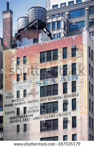 NEW YORK CITY - JUNE 14, 2015: faded ads on old brick building on the Eighth Avenue and 39th Street - stock photo