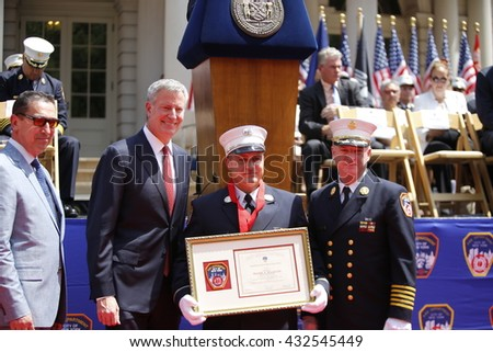 NEW YORK CITY - JUNE 1 2016: Mayor de Blasio & Commissioner Daniel Nigro presided over FDNY medal day on the steps of city hall. FDNY lieutenant Adam Vilagos with award