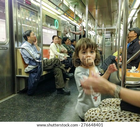 NEW YORK CITY - JUNE 9: Tourists and commuters in subway wagon on June 9, 2013 in NYC.The NYC Subway is one of the oldest and most extensive public transportation systems in the world and 468 stations - stock photo