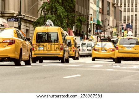 NEW YORK CITY - JUNE 13, 2013: Yellow cabs along Manhattan avenue. More than 13,000 taxis populate the city. - stock photo