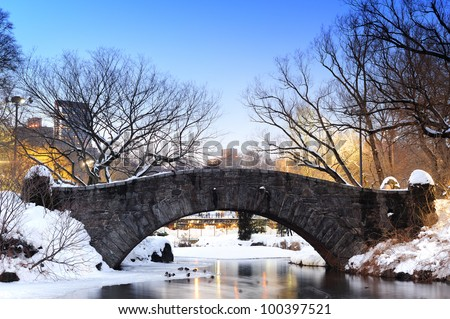 New York City Manhattan Central Park in winter with bridge over lake with snow, ducks and light at dusk. - stock photo