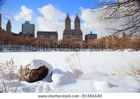 New York City Manhattan Central Park in winter with ice and snow over lake with rocks, skyscrapers and blue cloudy sky at dusk. - stock photo