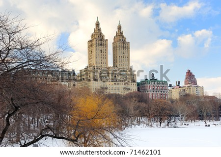 New York City Manhattan Central Park in winter with ice and snow over lake with skyscrapers and blue cloudy sky at dusk. - stock photo