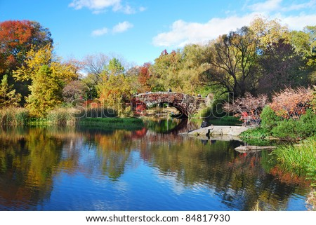 New York City Manhattan Central Park panorama in Autumn lake with bridge skyscrapers and colorful trees with reflection. - stock photo