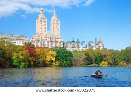 New York City Manhattan Central Park panorama in Autumn lake with skyscrapers and colorful trees over with reflection with boat. - stock photo