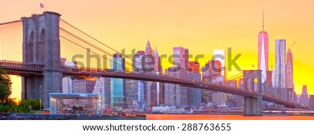 New York City, Manhattan downtown panorama with famous landmark Brooklyn Bridge at colorful sunset - stock photo