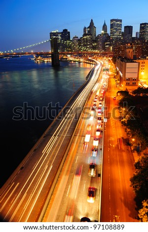 New York City Manhattan downtown skyline aerial view at dusk with skyscrapers lit over East River with reflections. - stock photo