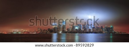 New York City Manhattan downtown skyline at night from Liberty Park with light beams in memory of September 11 viewed from New Jersey waterfront. - stock photo