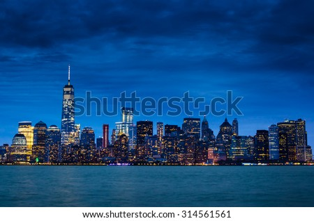 New York City Manhattan downtown skyline at night with illuminated skyscrapers and cloudy sky.