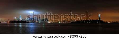 New York City Manhattan downtown skyline at night with statue of liberty and light beams in memory of September 11 viewed from New Jersey waterfront. - stock photo