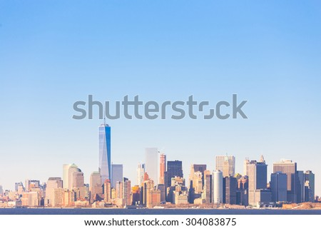 New York City Manhattan downtown skyline at sunset with skyscrapers illuminated over Hudson River panorama. Horisontal composition, copy space. - stock photo