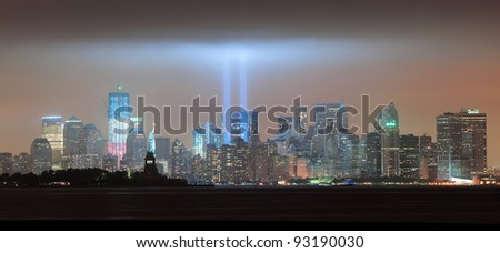 New York City Manhattan downtown skyline panorama at night with statue of liberty and light beams in memory of September 11 viewed from New Jersey waterfront.