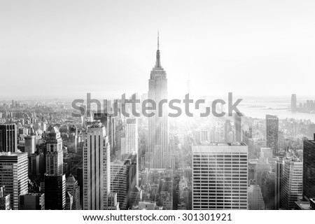 New York City. Manhattan downtown skyline with illuminated Empire State Building and skyscrapers at sunset. Vertical composition. Sunbeams and lens flare. Black and white image. - stock photo