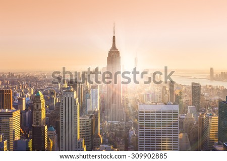 New York City. Manhattan downtown skyline with illuminated Empire State Building and skyscrapers at sunset. Horizontal composition. Warm evening colors. Sunbeams and lens flare. - stock photo