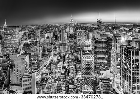 New York City. Manhattan downtown skyline with illuminated Empire State Building and skyscrapers at dusk. Black and white image. - stock photo