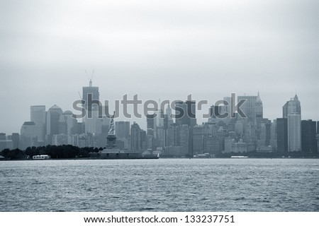 New York City Manhattan downtown skyline with statue of liberty over river.
